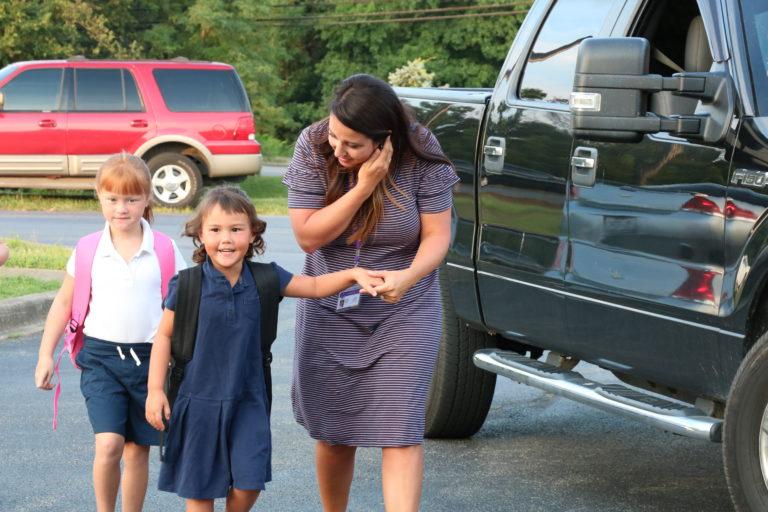 Kelsey Monin helps a student walk into school